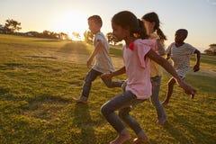 Vier Kinder, die barfuß in einen Park laufen stockfotos