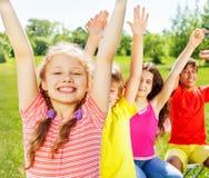 Vier Kinder, die in der Reihe mit den Händen oben sitzen Lizenzfreie Stockbilder