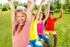 Vier Kinder, die in der Reihe mit den Händen oben sitzen Lizenzfreie Stockfotografie