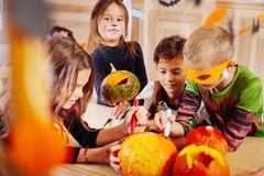 Vier Kinder, die Halloween tragen, kostümiert das Gefühl, das im Kindergarten unterhalten wird lizenzfreie stockbilder
