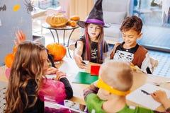 Vier Kinder, die Spaß beim Feiern von Halloween im Kindergarten haben lizenzfreie stockbilder