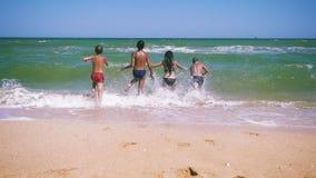 Vier Kinder, die zum Meer vom Strand laufen stock video