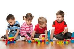 Vier Kinder spielen auf dem Fußboden Stockbilder