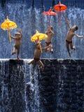 Vier Kinder springen mit Regenschirmen stockfotografie
