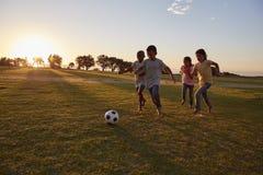 Vier kinderen die een bal achtervolgen tijdens een spel op een gebied stock foto