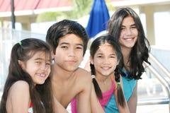 Vier kinderen door de poolkant Royalty-vrije Stock Afbeelding
