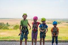Vier kinderen dragen helmen en beklimmen kleren en zijn bereid om hindernissen in een extreem park te overwinnen royalty-vrije stock foto