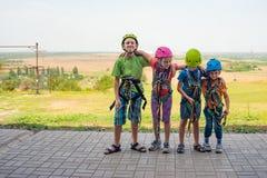 Vier kinderen dragen helmen en beklimmen kleren en zijn bereid om hindernissen in een extreem park te overwinnen royalty-vrije stock afbeeldingen