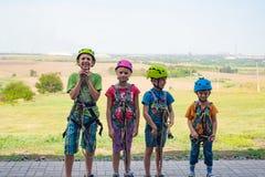 Vier kinderen dragen helmen en beklimmen kleren en zijn bereid om hindernissen in een extreem park te overwinnen royalty-vrije stock fotografie