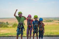 Vier kinderen dragen helmen en beklimmen kleren en zijn bereid om hindernissen in een extreem park te overwinnen royalty-vrije stock foto's