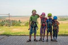 Vier kinderen dragen helmen en beklimmen kleren en zijn bereid om hindernissen in een extreem park te overwinnen stock afbeelding