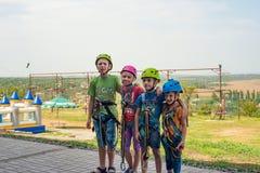 Vier kinderen dragen helmen en beklimmen kleren en zijn bereid om hindernissen in een extreem park te overwinnen royalty-vrije stock afbeelding