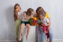 Vier kinderen met verse groenten gezond voedsel stock fotografie