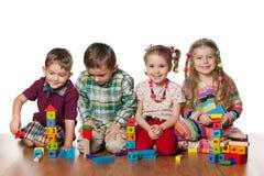 Vier kinderen spelen op de vloer Stock Foto's