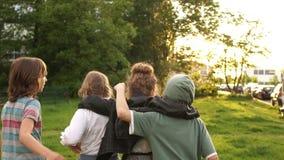 Vier klasgenoten koesterden elkaar en kwamen de afstand tegen tegen de achtergrond van groene bomen en zonsondergang school stock footage