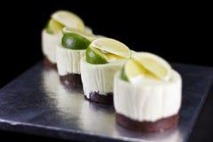 Vier kleine die cakes met kalkwiggen worden verfraaid Stock Foto's