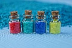 Vier kleine glasflessen met gekleurd zand Stock Afbeeldingen