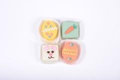 Vier kleine heldere Pasen-cakes in een vorm van konijntje en eieren Royalty-vrije Stock Foto