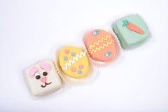 Vier kleine heldere Pasen-cakes in een vorm van konijntje en eieren Stock Fotografie