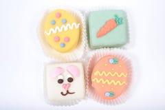 Vier kleine heldere Pasen-cakes in een vorm van konijntje en eieren Stock Foto's