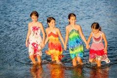 Vier kleine Mädchen, die Spaß im Wasser auf Ada-bojana, Montene haben Stockbild