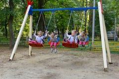 Vier Klone nettes kleines Mädchen, das auf Schwingen schwingt Stockbilder