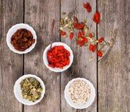 Vier kommen met de gezonde snacks, rozijnen, zonnebloemzaden, pitten van pompoenzaden en wolf-bessen op houten achtergrond stock afbeelding