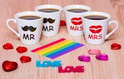 Vier koppen van koffie voor vrienden, regenboogvlag, liefde en harten Stock Fotografie