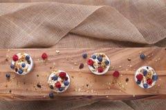 Vier Koppen Yoghurt, Granola, Bosbessen en Frambozen op Hout en Jute met Exemplaarruimte Stock Afbeelding