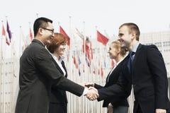 Vier lächelnde Geschäftsleute, die draußen Hände, Peking treffen und rütteln Stockfoto