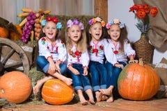 Vier lächelnde Mädchenzwillingsschwestern in den ukrainischen Kränzen, die auf Heuschobern sitzen Herbstdekor, Ernte mit Kürbisen lizenzfreie stockbilder