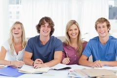 Vier lächelnde Studenten, die die Kamera untersuchen Stockfotografie