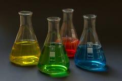 Vier Laborflaschen mit Flüssigkeiten lizenzfreie stockfotos