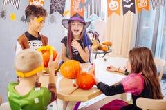 Vier lachende Kinder, welche die Kostüme spielen lustige Halloween-Spiele tragen lizenzfreie stockfotos