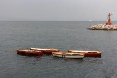 Vier leere Boote im Hafen gegen Leuchtturm und Weiß versenden auf horizone Vorderansicht von zwei Ladung-LKWas stockfoto