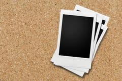 Vier leere Polaroide gestapelt und auf Korkenbrett hinzugefügt Lizenzfreie Stockfotos