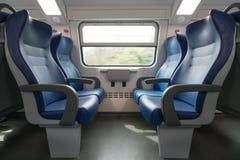 Vier lege blauwe zetels die elkaar in moderne Europese trein onder ogen zien royalty-vrije stock afbeeldingen
