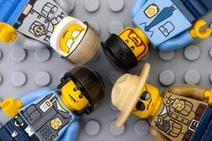 Vier Lego-Polizisten minifigures auf grauer Grundplatte Lizenzfreie Stockfotografie