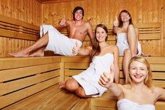 Vier Leute in den Saunaholdingdaumen stockbilder