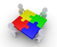 Vier Leute, die abgeschlossenes Puzzlespiel halten Stockbild
