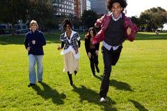 Vier Leute, die durch einen städtischen Park laufen Lizenzfreie Stockfotografie