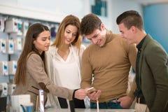 Vier Leute, die intelligente Telefone wählen Lizenzfreie Stockbilder