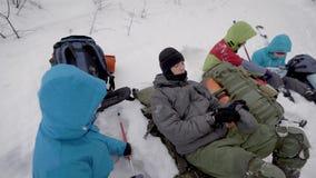 Vier Leute stehen w?hrend des Wintertrekkings im Wald still, liegen auf Schnee und ?berpr?fen Rucks?cke stock footage