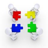 Vier Leuteholding-Puzzlespielstücke Lizenzfreie Stockbilder