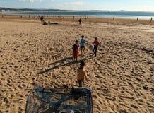 Vier lokale Kinder, die Strandfußball spielen stockfotografie