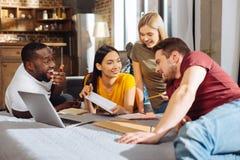 Vier lustige glückliche Studenten, die für Test sich vorbereiten Lizenzfreie Stockbilder