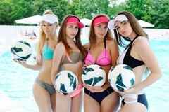 Vier Mädchen in Badeanzügen mit den Bällen auf dem Poolhintergrund Stockbild