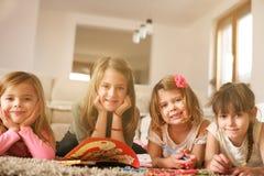 Vier Mädchen, die auf dem Boden liegen lizenzfreie stockfotografie