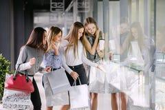Vier Mädchen, die im Einkaufszentrum kaufen stockfotos