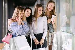 Vier Mädchen, die im Einkaufszentrum kaufen stockbild